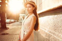 Το μοντέρνο και όμορφο κορίτσι σε ένα καπέλο περπατά μέσω της ηλιόλουστης πόλης Στοκ εικόνα με δικαίωμα ελεύθερης χρήσης
