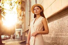 Το μοντέρνο και όμορφο κορίτσι σε ένα καπέλο περπατά μέσω της ηλιόλουστης πόλης Στοκ Εικόνα