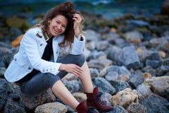 Το μοντέρνο κορίτσι έντυσε στο άσπρο σακάκι και το ευρύ παντελόνι που θέτουν κοντά στη θάλασσα το βράδυ στοκ φωτογραφίες με δικαίωμα ελεύθερης χρήσης