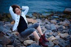 Το μοντέρνο κορίτσι έντυσε στο άσπρο σακάκι και το ευρύ παντελόνι που θέτουν κοντά στη θάλασσα το βράδυ στοκ εικόνα με δικαίωμα ελεύθερης χρήσης