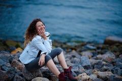 Το μοντέρνο κορίτσι έντυσε στο άσπρο σακάκι και το ευρύ παντελόνι που θέτουν κοντά στη θάλασσα το βράδυ στοκ εικόνες
