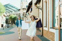 Το μοντέρνο κορίτσι με τις αγορές τοποθετεί το περπάτημα στην οδό σε σάκκο, ο φίλος της που περπατά πίσω Στοκ Φωτογραφίες
