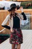 Το μοντέρνο κορίτσι που ντύνεται σε ένα μαύρο turtleneck, ένα μπεζ ακρωτήριο, μια μοντέρνα κοντά φούστα και ένα μαύρο καπέλο με τ στοκ φωτογραφίες