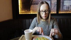 Το μοντέρνο κορίτσι στα γυαλιά κόβει ένα μικρό κομμάτι του punkake, το βυθίζει στο γλυκό σιρόπι φρούτων και πίνει το καυτό τσάι μ απόθεμα βίντεο
