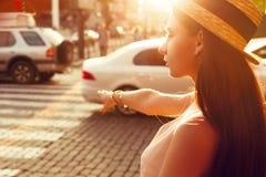 Το μοντέρνο κορίτσι στην ηλιόλουστη πόλη πιάνει ένα ταξί Στοκ Εικόνες