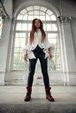 Το μοντέρνο κορίτσι Dreadlocks έντυσε στο άσπρο πουκάμισο και το μαύρο παντελόνι δέρματος που θέτουν στην πηγή του παλαιού μεγάλο στοκ φωτογραφία με δικαίωμα ελεύθερης χρήσης