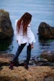 Το μοντέρνο κορίτσι Dreadlocks έντυσε στο άσπρο σακάκι και το μαύρο παντελόνι δέρματος που θέτουν κοντά στη θάλασσα το βράδυ στοκ εικόνα με δικαίωμα ελεύθερης χρήσης