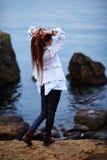 Το μοντέρνο κορίτσι Dreadlocks έντυσε στο άσπρο σακάκι και το μαύρο παντελόνι δέρματος που θέτουν κοντά στη θάλασσα το βράδυ στοκ φωτογραφίες
