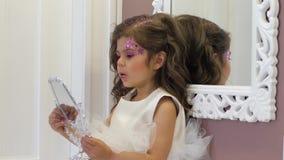 Το μοντέρνο παιδί με το όμορφα hairstyle και τα τσέκια στο πρόσωπο κρατά ότι ο καθρέφτης παραδίδει μέσα το δωμάτιο φιλμ μικρού μήκους