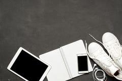 Το μοντέρνο περιστασιακό επίπεδο βάζει των άσπρων πάνινων παπουτσιών στο μαύρο υπόβαθρο με το τηλέφωνο, ακουστικά, ταμπλέτα, βιβλ Στοκ φωτογραφίες με δικαίωμα ελεύθερης χρήσης