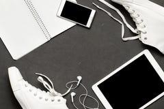 Το μοντέρνο περιστασιακό επίπεδο βάζει των άσπρων πάνινων παπουτσιών στο μαύρο υπόβαθρο με το τηλέφωνο, ακουστικά, ταμπλέτα, βιβλ Στοκ φωτογραφία με δικαίωμα ελεύθερης χρήσης