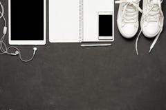 Το μοντέρνο περιστασιακό επίπεδο βάζει των άσπρων πάνινων παπουτσιών στο μαύρο υπόβαθρο με το τηλέφωνο, ακουστικά, ταμπλέτα, βιβλ Στοκ Εικόνες