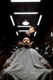 Το μοντέρνο barbershop Ο κουρέας μόδας τακτοποιεί τη γενειάδα της βάναυσης συνεδρίασης ατόμων στην πολυθρόνα στοκ φωτογραφίες