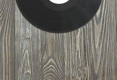 Το μουσικό ακουστικό πιάτο βρίσκεται σε έναν ξύλινο πίνακα Στοκ Φωτογραφία