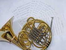 Το μουσικό γαλλικό κέρατο οργάνων βρίσκεται σε ένα άσπρο υπόβαθρο με τις σημειώσεις στοκ εικόνες