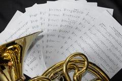 Το μουσικό γαλλικό κέρατο οργάνων βρίσκεται σε ένα μαύρο υπόβαθρο με τις σημειώσεις Στοκ Εικόνες