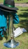 Το μουσικό όργανο ορείχαλκου έβαλε στο έδαφος με το καπέλο όταν παίρνει η ζώνη Στοκ Εικόνες