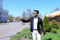 Το μουσουλμανικό αγόρι που εξετάζει το νέο τηλέφωνο και που παρουσιάζει σημάδι ειρήνης παραδίδει σε αργή κίνηση Στοκ Φωτογραφία