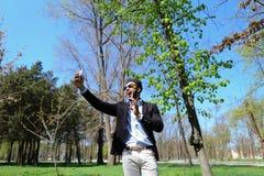 Το μουσουλμανικό αγόρι που εξετάζει το νέο τηλέφωνο και που παρουσιάζει σημάδι ειρήνης παραδίδει σε αργή κίνηση Στοκ φωτογραφία με δικαίωμα ελεύθερης χρήσης