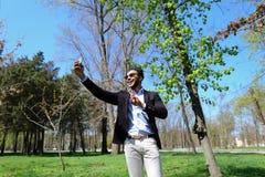 Το μουσουλμανικό αγόρι που εξετάζει το νέο τηλέφωνο και που παρουσιάζει σημάδι ειρήνης παραδίδει σε αργή κίνηση Στοκ Εικόνες