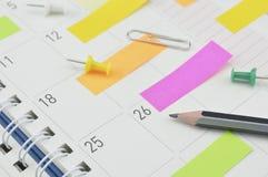 Το μολύβι με τη θέση αυτό σημειώνει και καρφίτσα στη σελίδα επιχειρησιακών ημερολογίων στοκ εικόνες