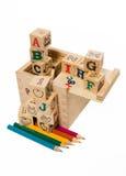 Το μολύβι χρώματος τακτοποιεί κάτω από τον ξύλινο φραγμό αλφάβητου Στοκ Φωτογραφία