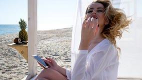 Το μπανγκαλόου, αέρας αναπτύσσει το άσπρο ύφασμα, το όμορφο κορίτσι κάνει selfie επάνω απόθεμα βίντεο