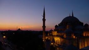 Το μπλε μουσουλμανικό τέμενος μετά από το ηλιοβασίλεμα άναψε επάνω δίπλα σε έναν δρόμο με τα οχήματα φιλμ μικρού μήκους
