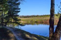 Το μπλε νερό του ποταμού και ο μπλε ουρανός χωρίς σύννεφα Μια θέση που χαλαρώνει έξω από την πόλη Στοκ εικόνα με δικαίωμα ελεύθερης χρήσης