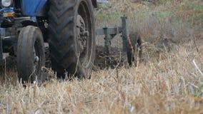 Το μπλε τρακτέρ οργώνει επίγεια furrows χάλυβα στα τέλη του φθινοπώρου στον τομέα φιλμ μικρού μήκους