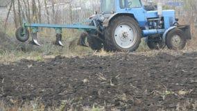 Το μπλε τρακτέρ οργώνει επίγεια furrows χάλυβα στα τέλη του φθινοπώρου στον τομέα απόθεμα βίντεο