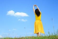 το μπλε φόρεμα χαλαρώνει τη γυναίκα ουρανού κίτρινη Στοκ Φωτογραφίες
