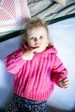 Το μπλε-eyed χαριτωμένο κορίτσι σε ένα ρόδινο πουλόβερ σκέφτεται στοκ εικόνες