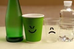 Το μπουκάλι γυαλιού με το καθαρό ορυκτό πόσιμο νερό και ένα έγγραφο κοιλαίνουν και ένα γυαλί με ένα πλαστικό μπουκάλι στοκ φωτογραφία