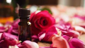 Το μπουκάλι του πετρελαίου αρώματος με το κόκκινο αυξήθηκε και των πετάλων τριαντάφυλλων στην ξύλινη επιφάνεια, επιλεγμένη εστίασ στοκ φωτογραφίες