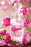 Το μπουκάλι αρώματος, αυξήθηκε λουλούδια. SPA aromatherapy Στοκ Φωτογραφία
