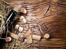 Το μπουκάλι κρασιού και βουλώνει στον ξύλινο πίνακα Στοκ Εικόνες
