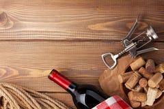 Το μπουκάλι κόκκινου κρασιού, βουλώνει και ανοιχτήρι πέρα από τον ξύλινο πίνακα backgroun Στοκ Εικόνα