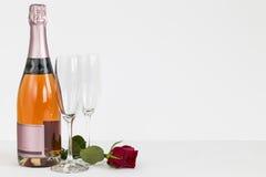 Το μπουκάλι σαμπάνιας ημέρας βαλεντίνων, φλάουτα και αυξήθηκε Στοκ Εικόνα