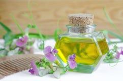 Το μπουκάλι του καλλυντικού πετρελαίου με τα λουλούδια εξάγει και ξύλινη χτένα τρίχας για τη φυσική προσοχή τρίχας Στοκ φωτογραφίες με δικαίωμα ελεύθερης χρήσης