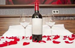 Το μπουκάλι του κόκκινου κρασιού, δύο γυαλιά και αυξήθηκε πέταλα σε ένα κρεβάτι - Ρωμαίος Στοκ Φωτογραφία