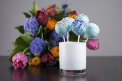 Το μπλε κέικ σκάει με ζωηρόχρωμο ψεκάζει με τα όμορφα λουλούδια στοκ φωτογραφία