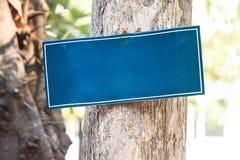 Το μπλε κενό σημάδι κρεμά στο δέντρο για το κείμενο μηνυμάτων Στοκ Φωτογραφία