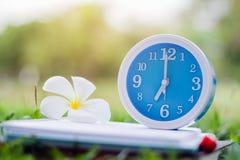 Το μπλε ξυπνητήρι στο σημειωματάριο με το υπόβαθρο φύσης, κλείνει επάνω το μπλε ξυπνητήρι Στοκ φωτογραφία με δικαίωμα ελεύθερης χρήσης