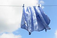Το μπλε πουκάμισο ατόμων ` s ξεραίνει στη σκοινί για άπλωμα Στοκ Εικόνες
