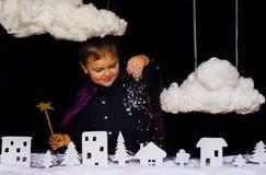 Το μυθικό παιδί ρίχνει το χιόνι πέρα από την πόλη στα Χριστούγεννα Στοκ Εικόνα