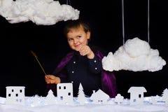 Το μυθικό παιδί ρίχνει το χιόνι πέρα από την πόλη στα Χριστούγεννα Στοκ Εικόνες