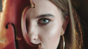 Το μυστήριο κορίτσι ανοίγει το μάτι και εξετάζει τη κάμερα με το βιολί σε μέρος του προσώπου απόθεμα βίντεο