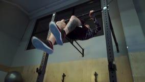 Το μυϊκό άτομο με μια δερματοστιξία στο πόδι του πηδά στο φραγμό και να κάνει μυς-επάνω φιλμ μικρού μήκους
