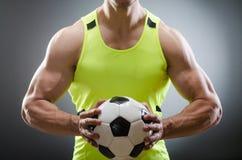 Το μυϊκό άτομο με τη σφαίρα ποδοσφαίρου Στοκ Εικόνες